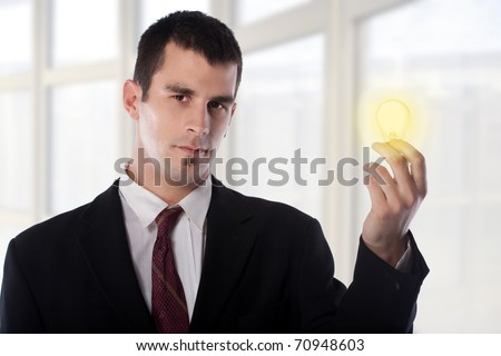 Young businessman holding a glowing bulb.Business solution concept