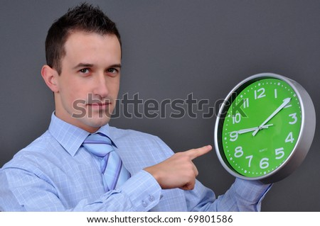 young businessman holding a green clock over grey - stock photo