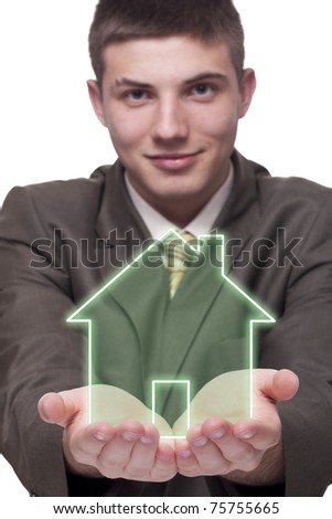 Young businessman holding a green house