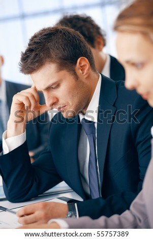 Young businessman holding a hand near his head, looking thoughtfully at something on the table in the office.