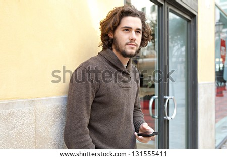 Young businessman holding a smart phone while standing by the entrance of an office building, outdoors.