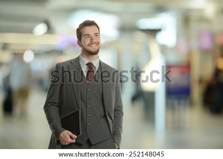 Young Businessman holding a tablet at the airport smiling - stock photo