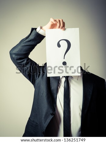 Young businessman holding a white billboard with a question mark on it - stock photo
