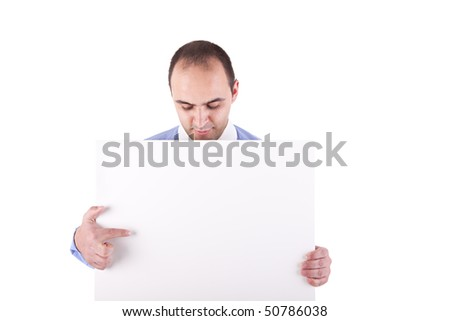 Young businessman holding a white board and pointing, looking down, isolated on white background - stock photo
