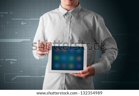 Young businessman holding a white modern tablet with blurry apps - stock photo