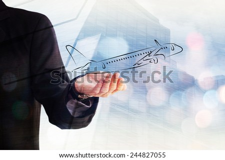 Young businessman holding an airplane in his hand