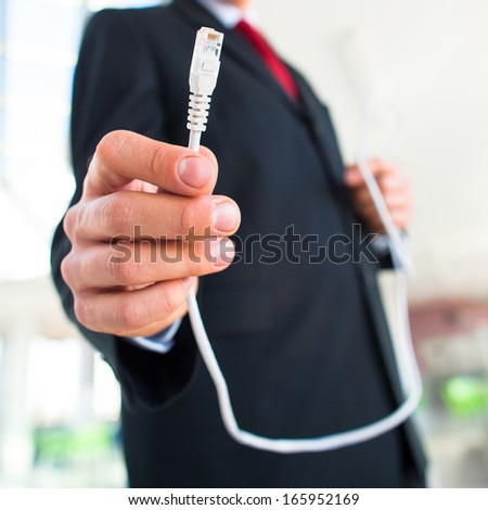 Young businessman holding an ethernet cable - stressing the importance of fast and reliable internet connection for a business (color toned image; shallow DOF) - stock photo