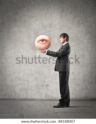 Young businessman holding an eye in his hands - stock photo