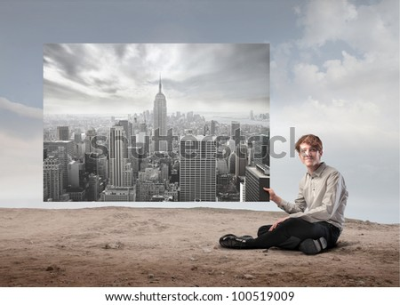 Young businessman holding an image of a big city - stock photo