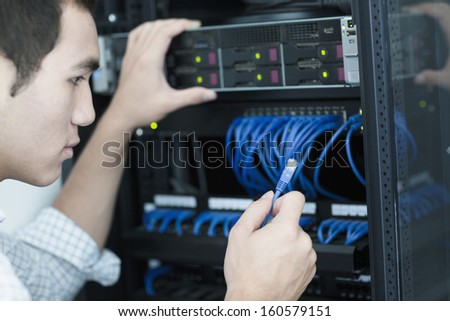 Young businessman holding and plugging in  computer cable