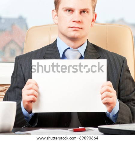 Young businessman holding blank paper - stock photo