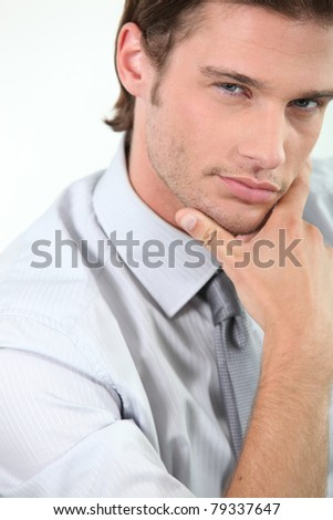 Young businessman holding chin - stock photo