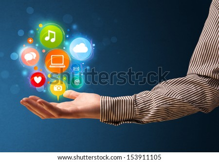 Young businessman holding colorful multimedia icons in his hand - stock photo