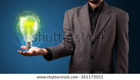 Young businessman holding glowing lightbulb in his hand - stock photo
