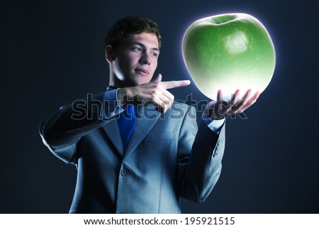 Young businessman holding green apple in hand
