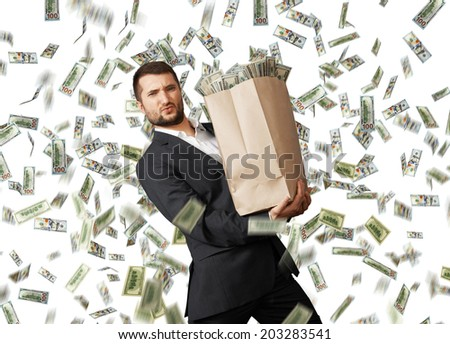 young businessman holding heavy paper bag with money under dollar's rain - stock photo