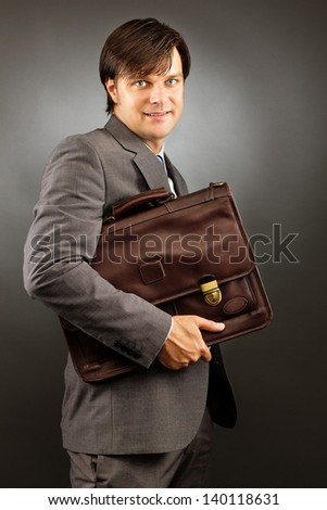 Young businessman holding his briefcase against gray background - stock photo