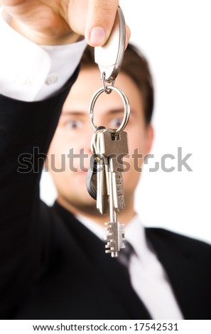 Young businessman holding keys. On white.