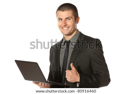 Young businessman holding laptop and showing thumps up sign, isolated on white background - stock photo