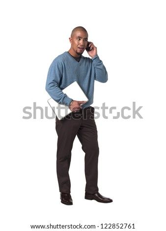 Young businessman holding laptop and talking on cellphone over white background - stock photo