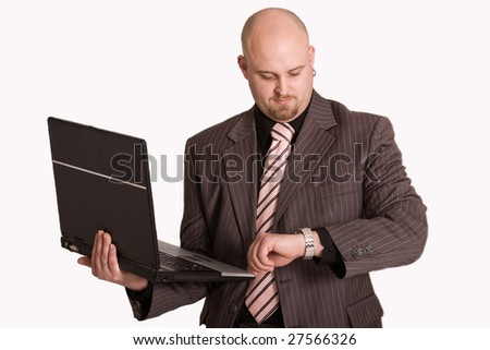 Young businessman holding laptop checking the time