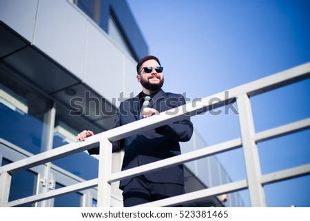 Young businessman holding metal fence in front of building
