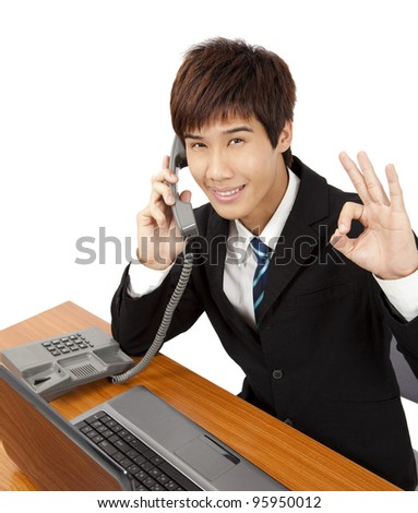 Young businessman  holding phone with OK hand gesture - stock photo