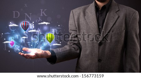 Young businessman holding shining letters and balloons in his hand