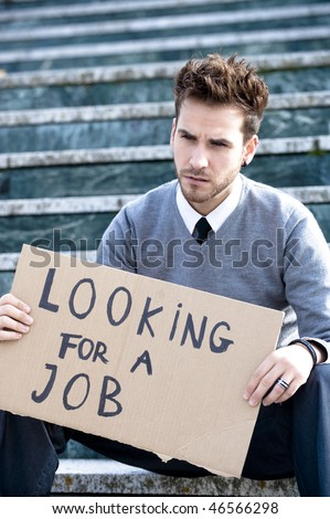 Young businessman holding sign Looking for a job