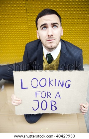 Young businessman holding sign Looking for a job from above - stock photo