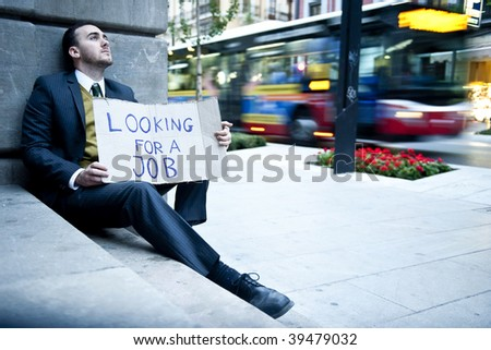 Young businessman holding sign Looking for a job with blurred background - stock photo