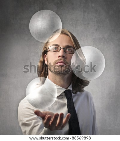 Young businessman holding some spheres over his hand