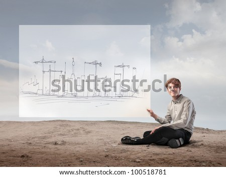 Young businessman holding the project for the construction of a city