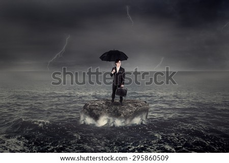 Young businessman holding umbrella while standing on the rock over ocean - stock photo