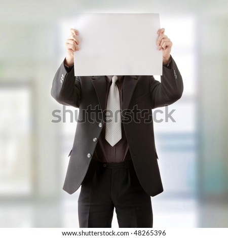 Young businessman holds blank signs. Focus on sign - stock photo