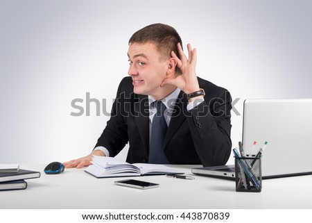 Young businessman holds his hand near ear on gray