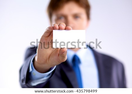 young businessman holds out his hand with a business card - stock photo