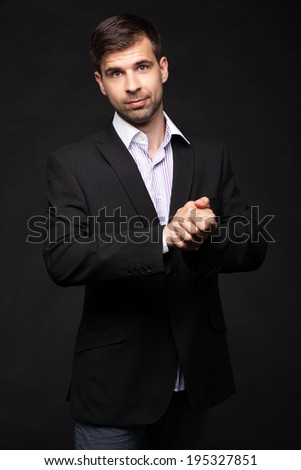 Young businessman in a black suit on dark background making a presentation