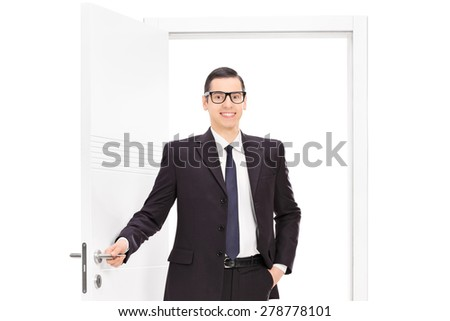 Young businessman in a black suit posing in front of an opened door isolated on white background - stock photo