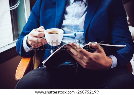 Young businessman in a blue jacket with a cup of coffee, reading a magazine in a cafe - stock photo