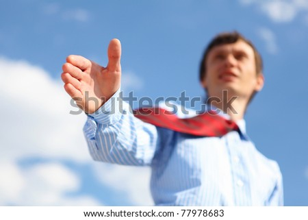 young businessman in a blue shirt and red tie giving a hand for a handshake - stock photo