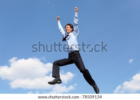young businessman in a blue suit jumping in the air against blue sky - stock photo