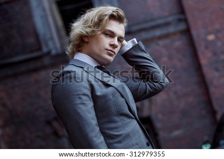 young businessman in a gray suit, business style,  portrait on the wall background - stock photo
