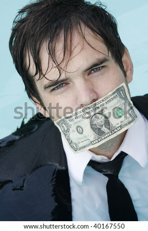 Young businessman in a pool with a dollar covering his mouth - stock photo