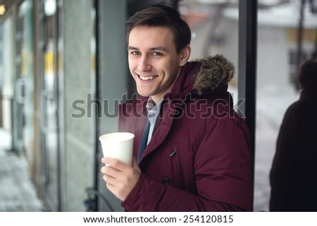 Young businessman in a suit and winter coat is drinking hot coffee at cold street with steam and bright smile on his face - stock photo