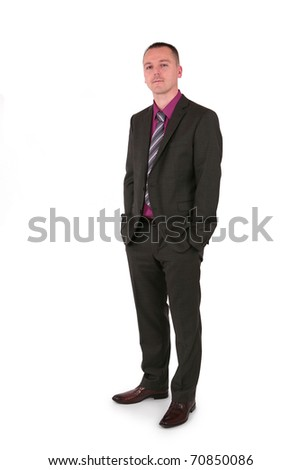 Young businessman in a suit holding his hands in pockets, isolated on white - stock photo