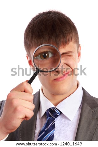 Young businessman in a suit looks through a magnifying glass on a white background