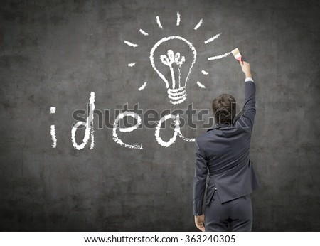 Young businessman in a suit painting the word 'idea' and a bulb with a brush in white on the black blackboard. Back view. Concept a new idea