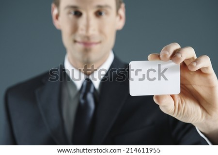 Young businessman in a suit presenting his blank white business card with copyspace for your credentials, marketing or branding with focus to the card - stock photo