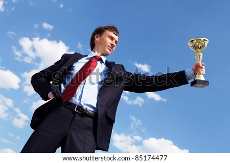 young businessman in a suit with a golden cup against blue sky - stock photo